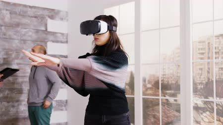 wizualizacja : Female architect using virtual reality goggles in empty apartment and real estate agent talking with client in the background.