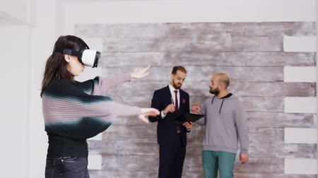 realidade : Female designer with virtual reality goggles in empty apartment while real estate agent is talking with the homeowner in the background. Vídeos