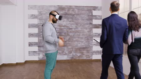 wizualizacja : Caucasian man using virtual reality headset in empty apartment while a woman is talking with real estate agent.
