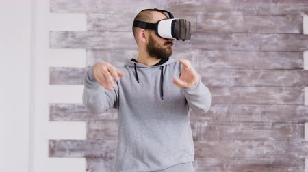 опыт : Caucasian home designer using virtual reality goggles inside of an empty apartment to decorate it in cyberspace