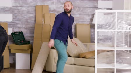 elkötelezettség : Caucasian young couple moving in their new home. Professional movers delivering cardboard boxes to door. Stock mozgókép