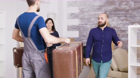 belongings : Man from delivery service arriving with suitcases of young couple in their new real estate. Couple moving in a new apartment. Stock Footage