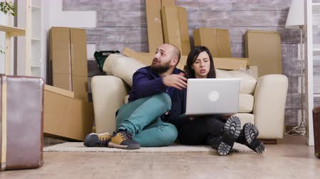 супруг : Couple sitting on the floor of new apartment and using laptop for online shopping.