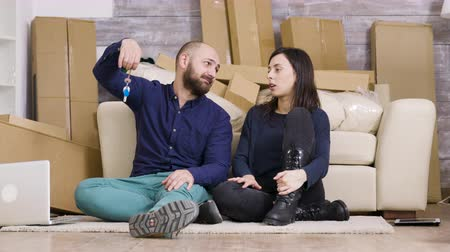 darovat : Beautiful young couple sitting on the floor of their new apartment. Boyfriend giving keys to her girlfriend. Cardboard boxes. Dostupné videozáznamy
