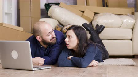 волнение : Happy couple sitting on the floor of their new apartment while making online shopping on laptop. Zoom in shot.