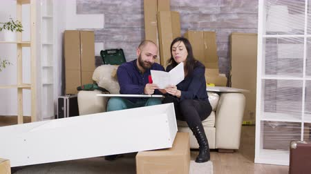 cabinet : Caucasian couple arguing while assembling a shelf in their new apartment. Girlfriend holding instructions.