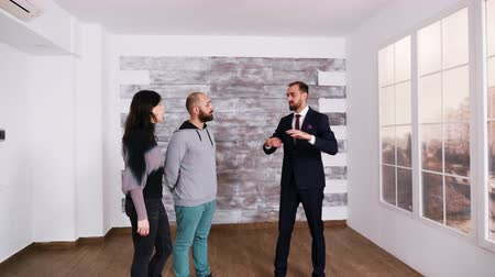 販売さ : Successful real estate agent talking with young couple in a brand new apartment. Zoom in shot