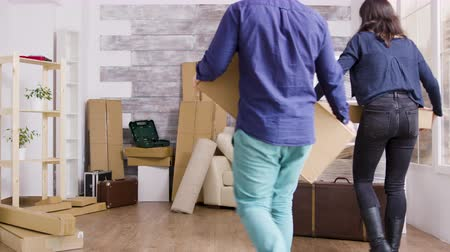 belongings : Young couple carrying boxes in their new apartment. Moving day for flat owners.