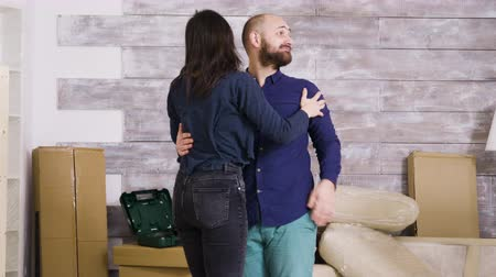závazek : Happy young couple hugging each other in their new apartment. Cardboard boxes in the background.