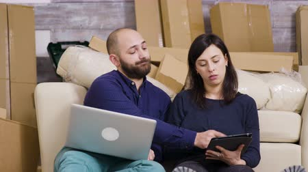 relocate : Couple sitting on the floor of their new apartment and making online shopping on laptop and tablet.