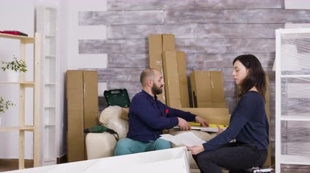 drawer : Couple assembling furniture in their new apartment. Couple do a high five after job done. Stock Footage