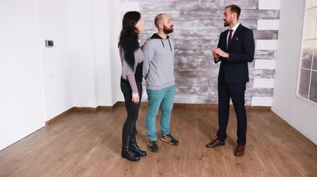 satılır : Bearded real estate agent in business suit showing new apartment to young couple.