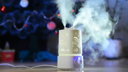 objeto : Ultrasonic humidifier in the house. Humidification. Vapor. Working humidifier on the blused background