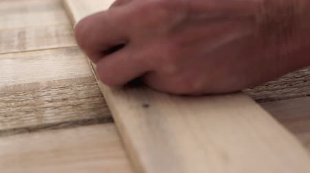 knotted : Carpenter nailing wood planks - close up