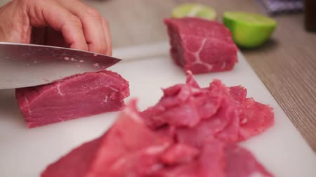 holding onto : HD 1080 static: chef chopping beef steak onto thin slices using sharp knife; close up;
