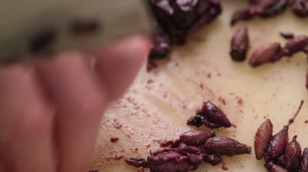 calamata olive : Chef removing pit from salted black olives using knife; close up,