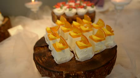 cukrozott : White square cakes, with a citrus layer, and candied fruit on top Stock mozgókép