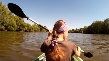 kayak : Young girl with a braid hairstyle rowing in a kayak. Ukraine, Southern Bug river