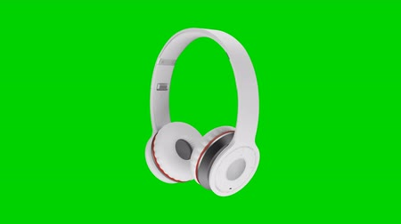 fejhallgató : White wireless headphones isolated on green screen background 3d illustration render Stock mozgókép