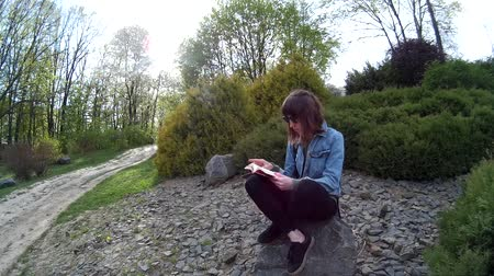 Beautiful girl reading a book while sitting on a rock in a park