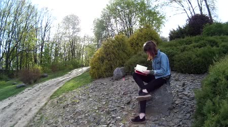 Beautiful girl reading a book while sitting on a rock in a park 3