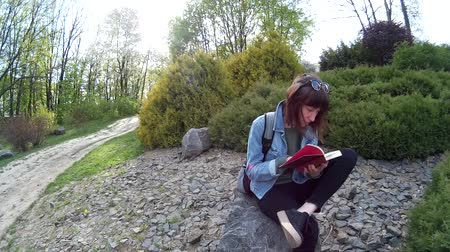 Beautiful girl reading a book while sitting on a rock in a park 2