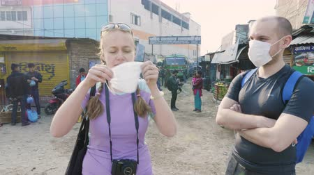 KATHMANDU, NEPAL - MARCH, 2018: Woman shows how to use respiratory mask in polluted city, march, 2018.