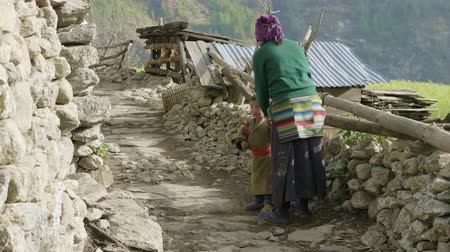 PROK, NEPAL - MARCH, 2018: Young mother holds the hand of her son. Stock Footage