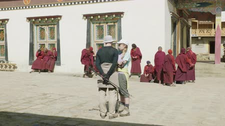 bhutan : SAMAGAON, NEPAL - MARCH, 2018: Tourists watch local Buddhist monk near monastery.