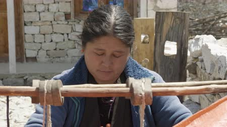 SHYALA, NEPAL - MARCH, 2018: Local woman manually braids the mat on an old homemade loom. Stock Footage