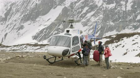 DHARMASALA, NEPAL - MARCH, 2018: Tourists get into the helicopter after the incident in mountains. Stock Footage