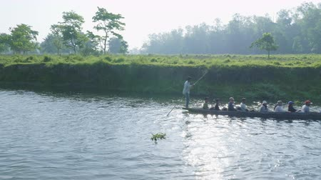 CHITWAN, NEPAL - MARCH, 2018: People in canoe safari on wooden boats in national park. Stock Footage