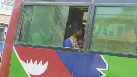 KATHMANDU, NEPAL - MARCH, 2018: Young mother holds her child on hands in a bus. Stock Footage