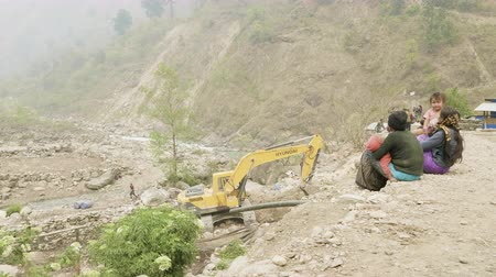 housenka : MANASLU, NEPAL - MARCH, 2018: Excavator repairs a stone road in the mountains.
