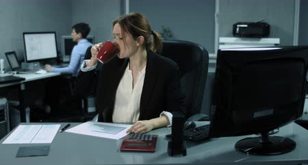 плохо : 4K: Two female employees are working on her computers in a modern office. The young woman in the foreground is deepened in the financial control. The woman in the background becomes annoyingly about whats on the screen. Стоковые видеозаписи