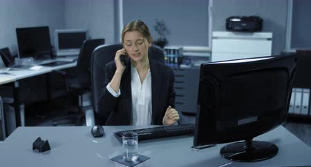 bancário : 4K: A young employee sits tensely in her office. A telephone call disturbs her computer work. She drinks a gulp of water and is annoyed. Vídeos