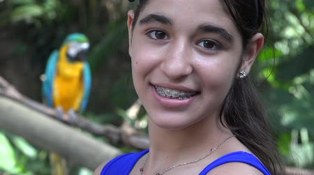 bretelle : Ragazza teenager sorridente con Parrot Filmati Stock