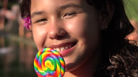 desszertek : Teen Hispanic Girl Eating Lollipop