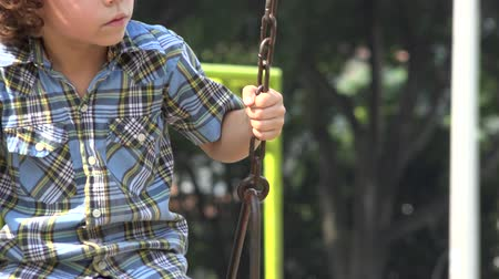 enrolar : Boy Swinging on Swing Set