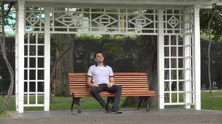 sieges : Happy Man Alone Sitting On Park Bench Vidéos Libres De Droits