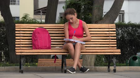 ławka : Female Student Sitting On Park Bench Drawing In Notebook Wideo