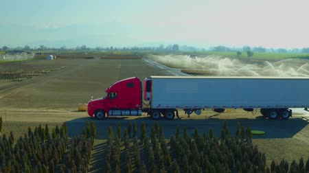 irrigate : Cab, truck, Farm Truck, Farm Lands Semi Cab Tractor Truck With Trailer Mountains Bakersfields California Wide Aerial Moving Sideways Jib up  Evening Sunset Stock Footage