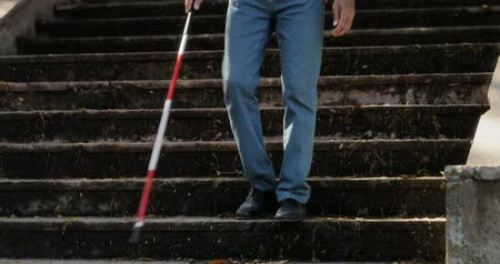 persiana : Hispanic blind man, latino people with disability, handicapped person and everyday life. Visually impaired man with walking stick, descending steps in city park Stock Footage