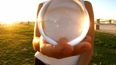 a girl plays contact juggling with a glass transparent ball