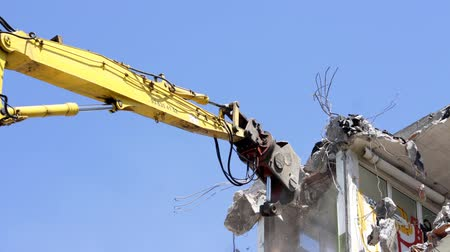 imha : a crane breaking down a building, looking a bit like like a dinosaur eating!