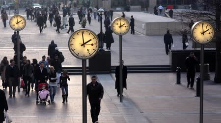 docklands : timelapse of crowds walking in london docklands with big clocks telling the time