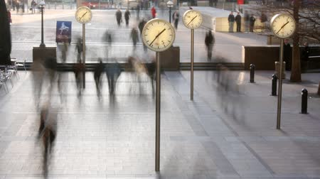 timelapse of crowds walking in london docklands with big clocks telling the time