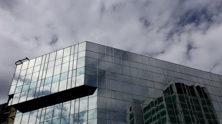 glass structure : reflections of clouds moving in glass mirrored office tower Stock Footage