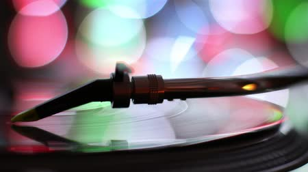 hiphop : close-up of the needle of dj record player, with abstract coloured lights in background Stock Footage