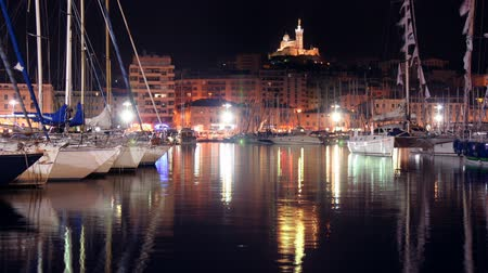 marseille : timelapse of the vieux port, marseille with notre dame de la garde church in background at night